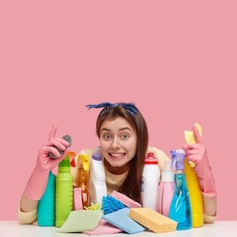 La vista dall'interno della giovane donna soddisfatta indossa la fascia, indica verso l'alto, mostra lo spazio libero per i tuoi contenuti pubblicitari