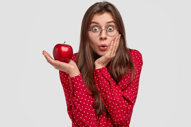 Indoor view of surprised caucasian lady touches cheek in amazement, holds red apple, wears spectacles