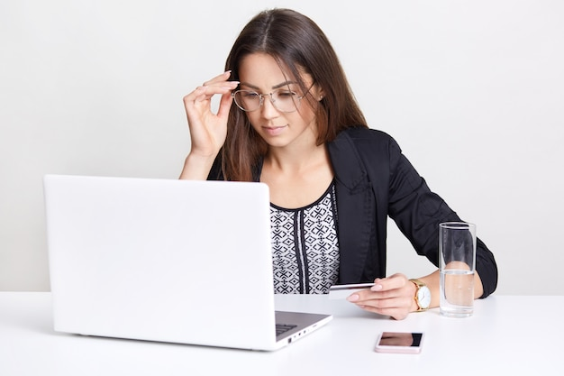 Indoor young caucasian woman types data of credit card on laptop computer, does online shopping, focused into screen, wears transparent glasses, isolated on white, drinks water