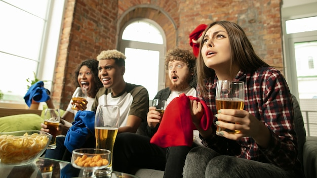 В помещении. взволнованные люди смотрят спортивный матч, чемпионат дома. многонациональная группа друзей.