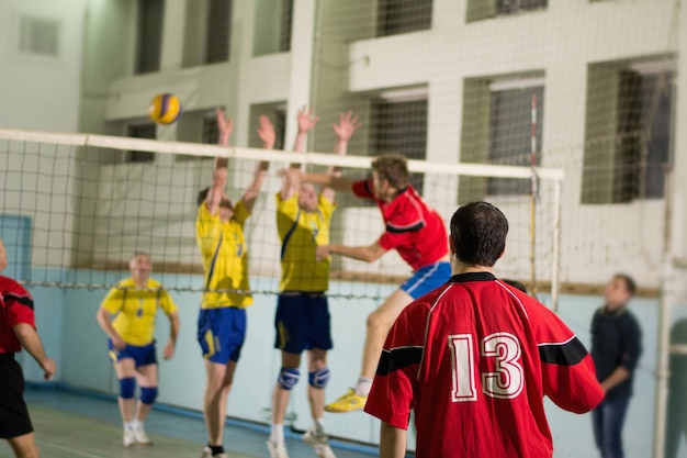 Indoors match between yellow and red uniform teams