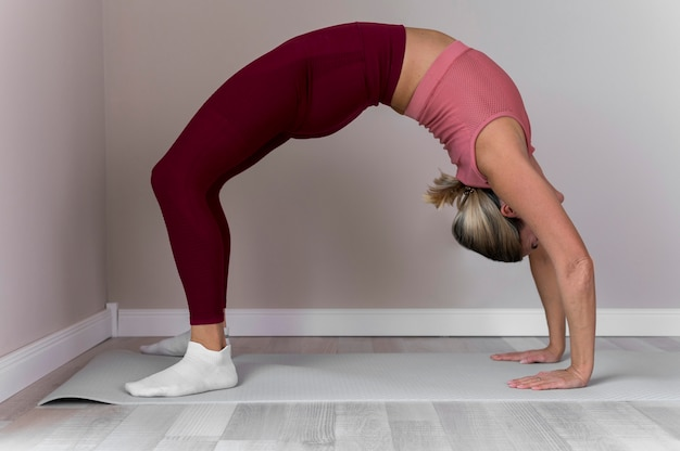 Indoors mature woman doing a hard stretching exercise