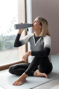 В помещении зрелая женщина пьет воду