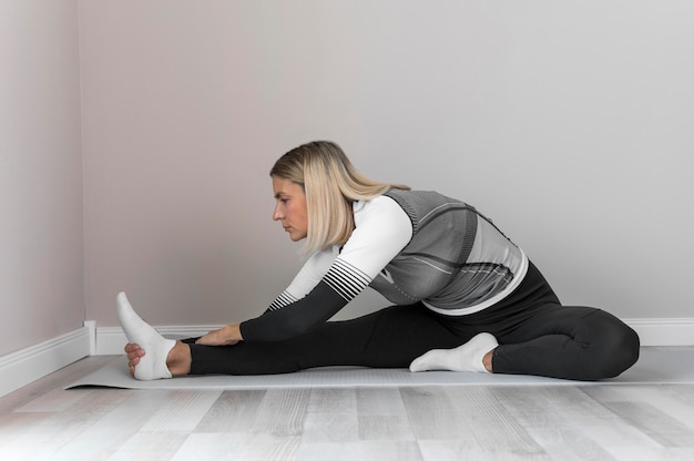 Indoors mature woman stretching her legs