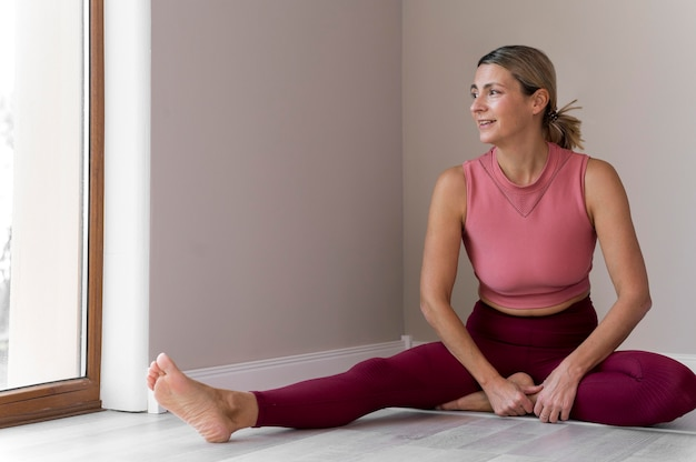 Indoors mature woman wearing pink sport clothes