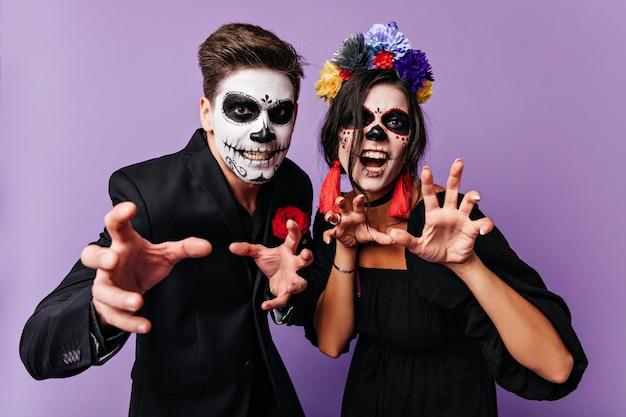 Снимок в помещении мужчины в костюме и женщины с короной из цветов, позирующих с пугающими выражениями лица.