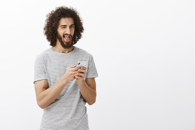 Indor shot of carefree happy young male student with beard and afro hairstyle, holding smartphone and winking