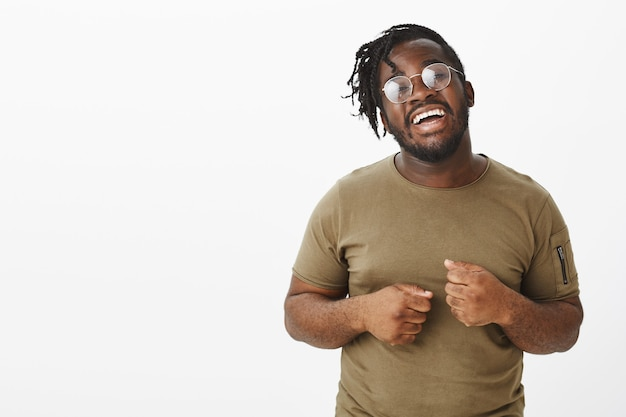 Indor shot of cheerful guy with glasses posing against the white wall