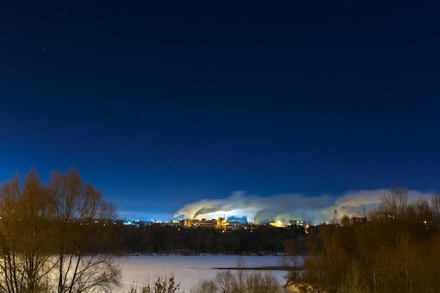 川のほとりの工業地帯。星空と夜の冬の風景。