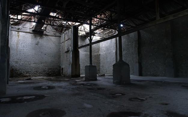 産業の背景。石の壁、壊れた屋根、さびた柱のある放棄された空の倉庫
