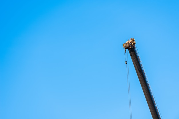 Industrial background with blue sky and a tall crane with the cable hanging.