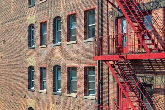 赤い非常階段のはしごで見た工業用れんが造りの建物