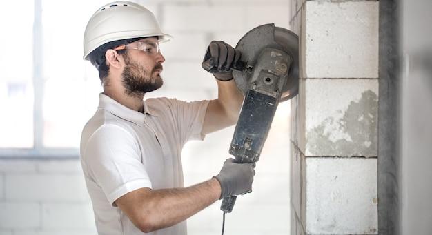Il costruttore industriale lavora con una smerigliatrice angolare professionale per tagliare i mattoni.