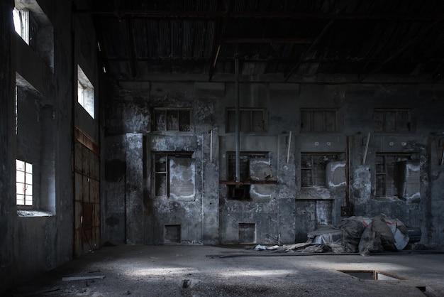 Фон промышленного здания. интерьер заброшенной фабрики с окрашенными бетонными стенами, кирпичными окнами и частями старого оборудования