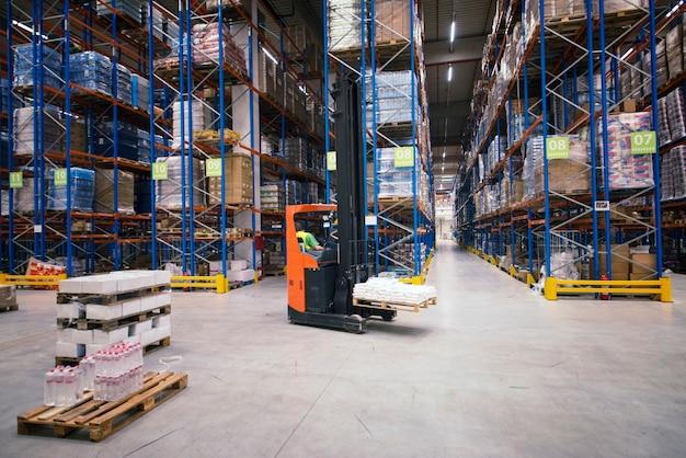 フォークリフトと商品と棚のあるパレットを備えた工業ビルの大きな倉庫のインテリア