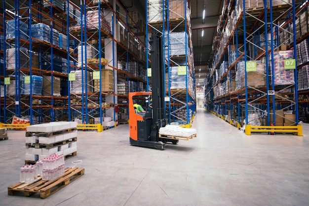Industrial building large warehouse interior with forklift and palette with goods and shelves