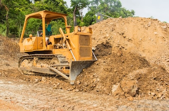 Industrial bulldozer moving earth and sand in sand pit or quarry