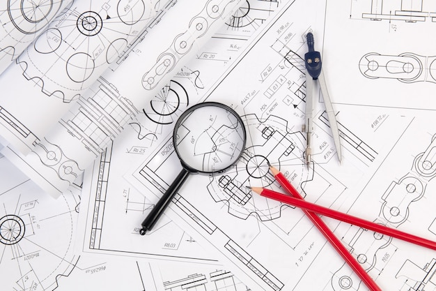 Industrial chain drawings, engineering compass, magnifying glass and pencils