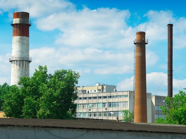 ロシアの工場の背景にある産業用煙突