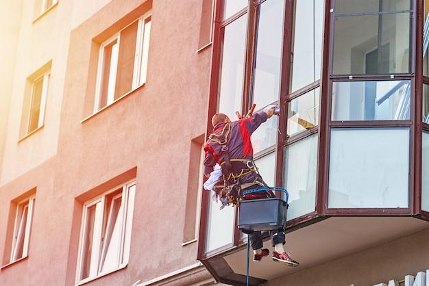 Промышленный альпинист чистит окно на здании в городе