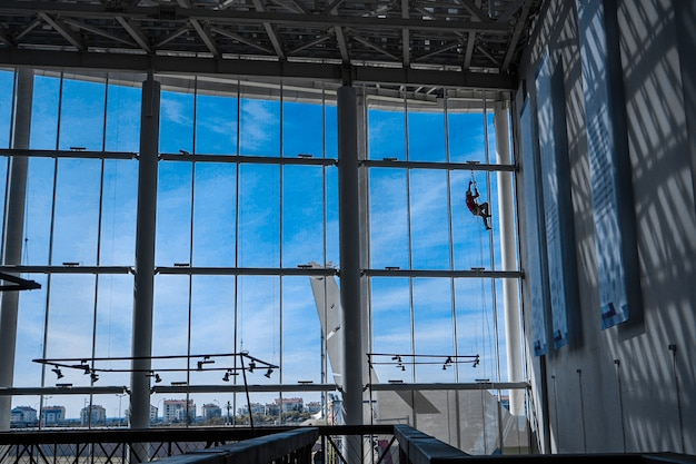 Industrial climber hangs from ropes inside building