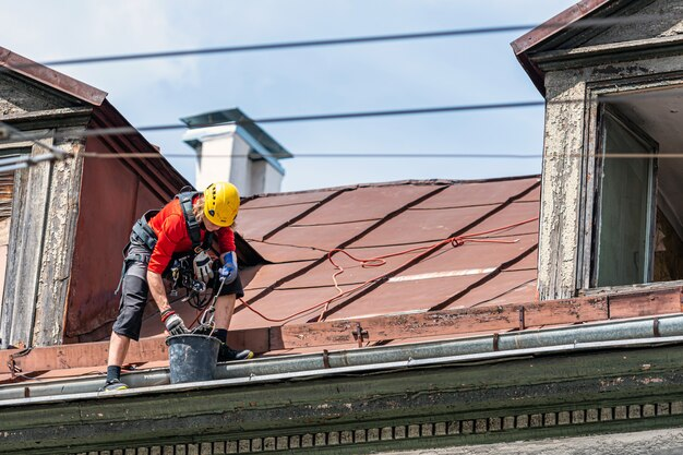 Industrial climber removes leaves and dirt from house rooftop rain gutter