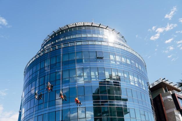Промышленные альпинисты моют окна дома снаружи.