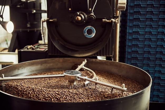 Industrial coffee roasting machine with brown freshly roasted coffee beans in cooling tray