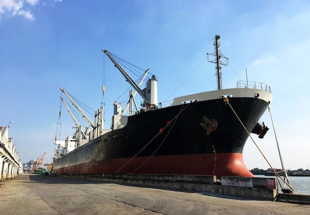 Промышленное грузовое судно контейнеровоз в гавани для логистического импорта и экспорта.