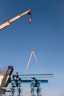 Industrial crane lifting steel frame in construction site