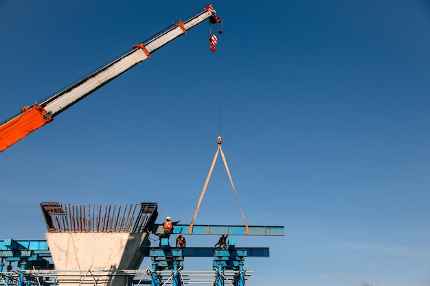 Industrial crane lifting steel frame in mega construction site of fly over project
