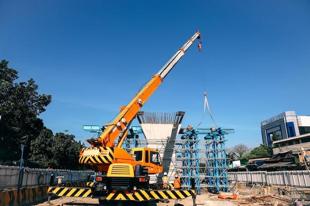 Industrial crane lifting steel frame in mega construction site