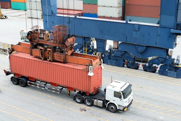 Industrial crane loading containers in a cargo freight ship.