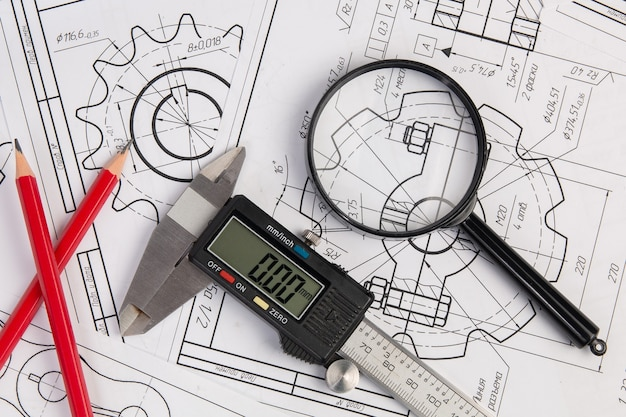 Industrial drawings, engineering magnifying glass, digital caliper and pencils