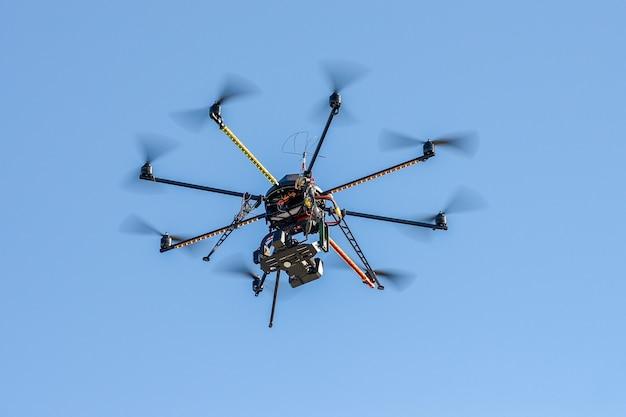 青い空のビデオカメラを備えた産業用ドローン