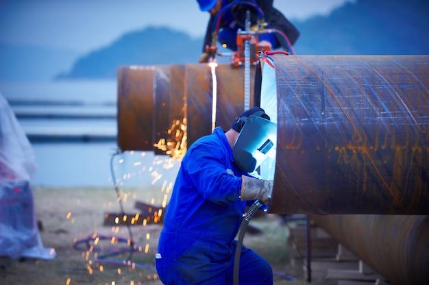 Промышленный сварщик электрода с лицевой защитой и синей полной сваркой стальной трубы в мастерской.