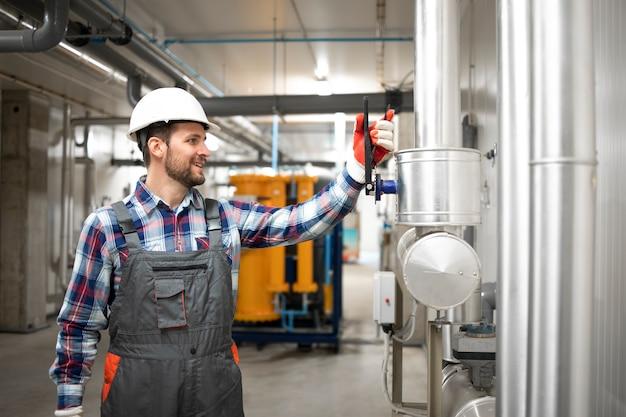 ガス設備をチェックするためにボイラー室の工場暖房システムのバルブを閉じる産業エンジニア