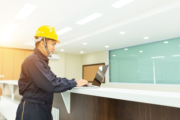 Industrial engineer in hard hat wearing safety jacket uses touchscreen laptop.