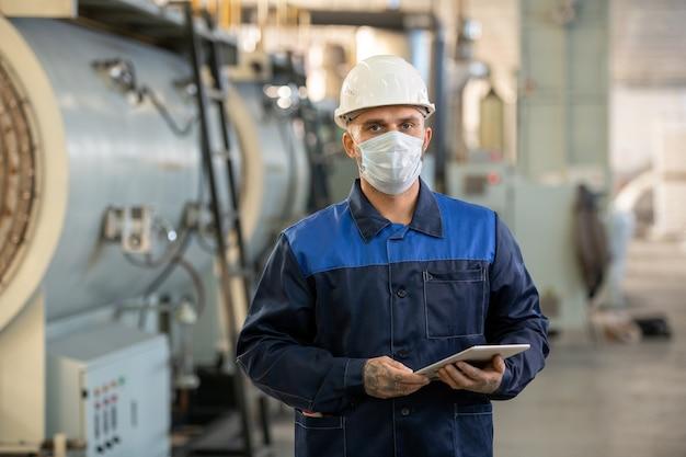 Инженер-технолог в официальной одежде и каске обсуждает детали машины с рабочими с помощью 3d-эскиза на планшете