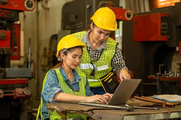 공장 현장에서 프로젝트를 계획하기 위해 노트북을 사용하여 안전을 착용하는 안전모의 산업 엔지니어.