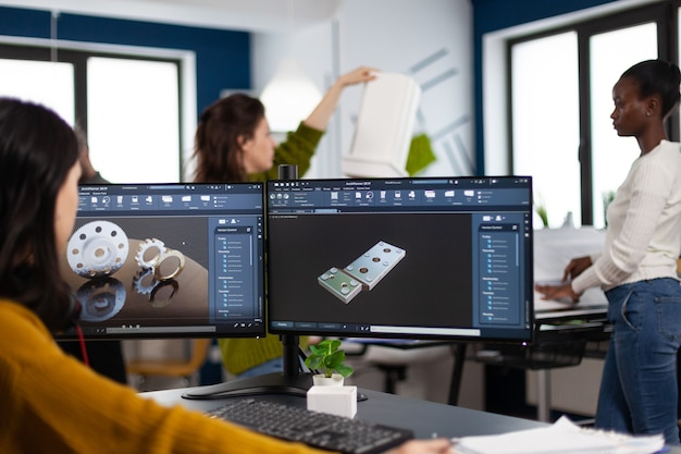 Industrial engineer woman working at pc with two monitors screens showing cad software