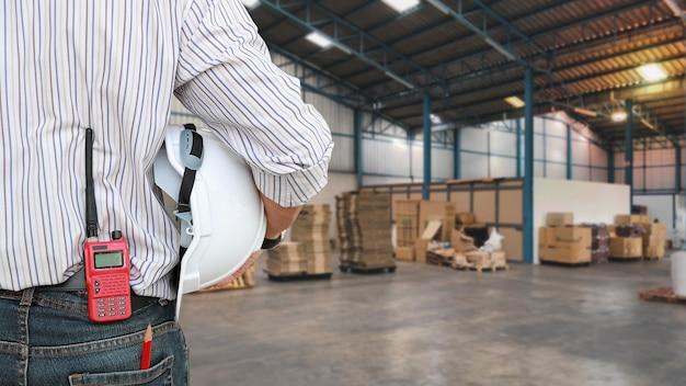 산업 공학 남자가 서서 안전모가 있는 청바지 패킷에 워키토키를 넣습니다. 흐릿한 대형 창고 배경으로 건설을 확인하는 작업자 여성. 개념 엔지니어는 현장에서 일합니다.