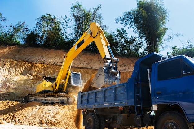 Industrial excavator and truck working on construction site to clear the land of sand and soil