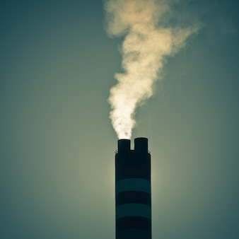 Industrial factory chimney with smoke against sky background. instagram style shot