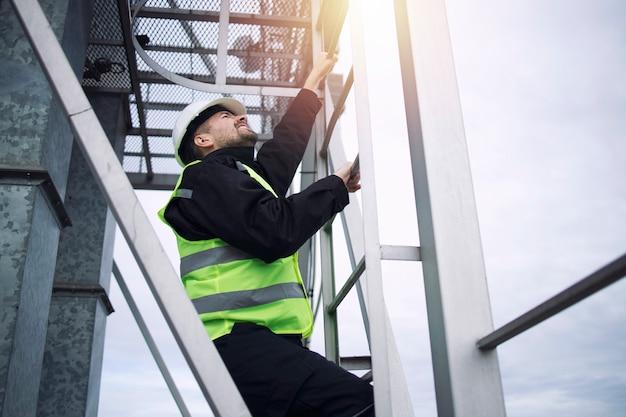 Рабочий-строитель промышленного завода поднимается по металлической лестнице производственного предприятия на закате.