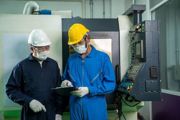 制御室の電気メーターパネルの近くで作業およびチェックしている産業工場の従業員。