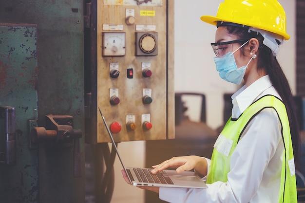 산업 공장 유지 보수 엔지니어 여자는 기계의 릴레이 보호 시스템을 검사하고 복사 공간이있는 노트북을 들고 있습니다. 산업, 유지 보수, 엔지니어링 및 건설 개념.