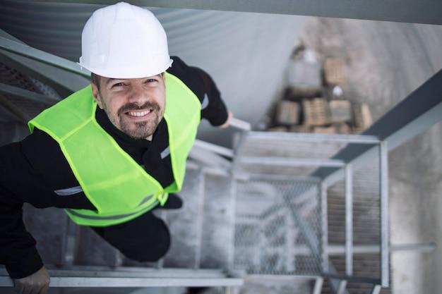 生産工場の金属製階段に立っている保護具の産業工場労働者