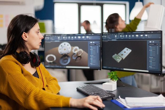 Промышленный инженер-женщина смотрит на персональный компьютер с настройкой двух мониторов, экраны, показывающие программное обеспечение сапр с 3d-прототипом металлической механической части зубчатых колес
