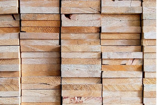 Промышленные головы деревянные прямоугольной формы из распиленного деревянного материала, которые уложены в квадрат на деревянном складе, хранят текстуру древесины и фон